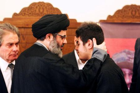 FILE PHOTO: Sayyed Hashem Safieddine, head of the Hezbollah Executive Council, pays his condolences to Ali Badreddine, the son of top Hezbollah commander Mustafa Badreddine who was killed in an attack in Syria, in Beirut's southern suburb