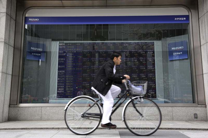 A man rides a bicycle past an electronic stock board of a securities firm in Tokyo Wednesday, April 2, 2014. Asian stock markets pushed higher Wednesday on signs of a pickup in the U.S. economy and expectations of further stimulus in Japan. Tokyo's Nikkei 225 closed at 14,946.32, after gaining 154.33 points, or 1.04 percent. (AP Photo/Eugene Hoshiko)