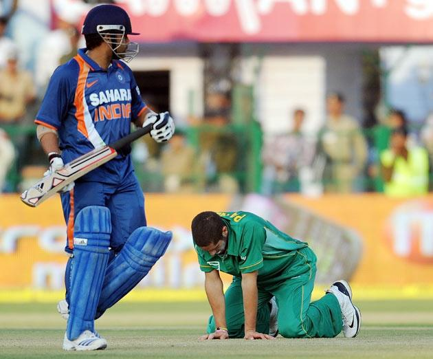 South African cricketer Wayne Parnell kneels on the ground as Indian cricketer Sachin Tendulkar (L) walks past him after scoring a world record breaking double century (200 runs) during the second One Day International (ODI) cricket match at the Captain Roop Singh Stadium in Gwalior on February 24, 2010. India played South Africa and finished with 401 runs for the loss of three wickets.  AFP PHOTO/ MANAN VATSYAYANA