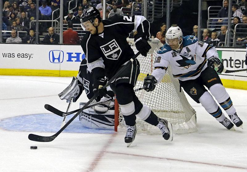Los Angeles Kings defenseman Slava Voynov (26), of Russia, clears the puck and is chased by San Jose Sharks center Patrick Marleau (12) in the first period of an NHL hockey game in Los Angeles Saturday, April 27, 2013. (AP Photo/Reed Saxon)