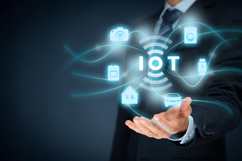 "A man extending a hand above float icons for different IoT applications and the letters ""IOT"""