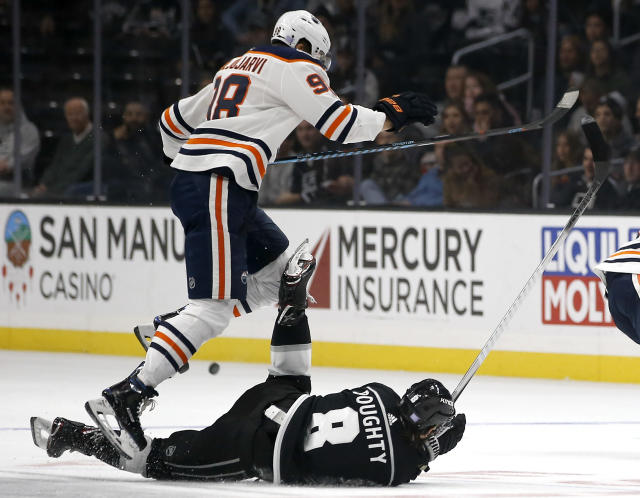 Edmonton Oilers right wing Jesse Puljujarvi, top, of Sweden, leaps over the fallen Los Angeles Kings defenseman Drew Doughty during the first period of an NHL hockey game in Los Angeles, Sunday, Nov. 25, 2018. (AP Photo/Alex Gallardo)