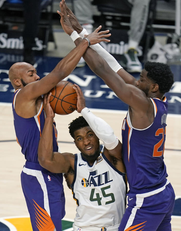Phoenix Suns' Jevon Carter, left, and Deandre Ayton, right, defend against Utah Jazz guard Donovan Mitchell (45) during the first half of an NBA preseason basketball game Saturday, Dec. 12, 2020, in Salt Lake City. (AP Photo/Rick Bowmer)