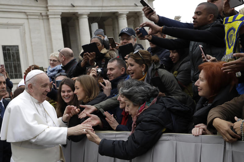 Pope Francis salutes faithful in St. Peter's Square at the Vatican before leaving after his weekly general audience, Wednesday, Feb. 26, 2020. (AP Photo/Alessandra Tarantino)