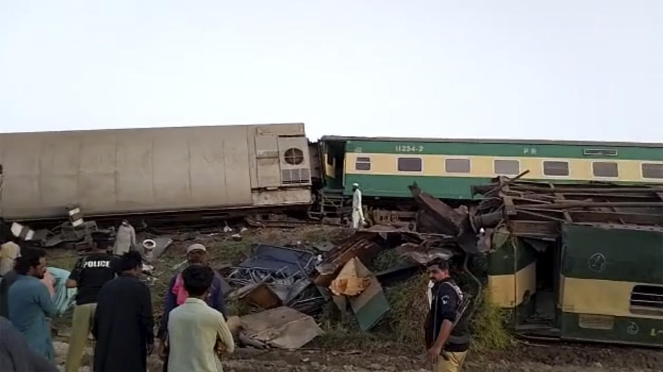 People gather around the scene of a collision between two trains in Ghotki.