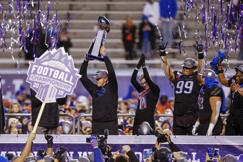 Boise State head coach Bryan Harsin holds up the Mountain West Championship trophy, left, as Boise State President Marlene Tromp, center, and Boise State linebacker Curtis Weaver, right, celebrate Boise State's 31-10 win over Hawaii in a NCAA college football game Saturday, Dec. 7, 2019, in Boise, Idaho. Boise State won 31-10. (AP Photo/Steve Conner)