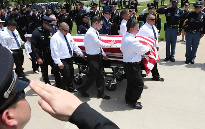 Pallbearers lead the flag draped coffin of slain Dallas police officer Patrick Zamarripa into place for an honor guard ceremony at Dallas-Fort Worth National Cemetery in Dallas, Saturday, July 16, 2016. Zamarripa was one of five officers killed last week by a lone gunman during a protest march in Dallas.