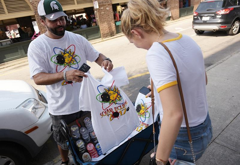 T-shirt vendor Jan Dahouas shows an eclipse t-shirt of his own design to a buyer on a street near the City Market in Charleston, South Carolina (AFP Photo/MANDEL NGAN)
