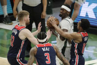 Milwaukee Bucks' Bobby Portis controls the ball while surrounded by Washington Wizards' Davis Bertans, Bradley Beal and Ish Smith, from left, during the first half of an NBA basketball game Wednesday, May 5, 2021, in Milwaukee. (AP Photo/Aaron Gash)