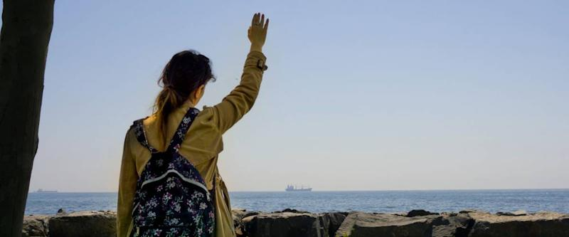 Sad woman or girl standing alone on the seaside and waving her hand to distant ship and horizon with feeling lonely.