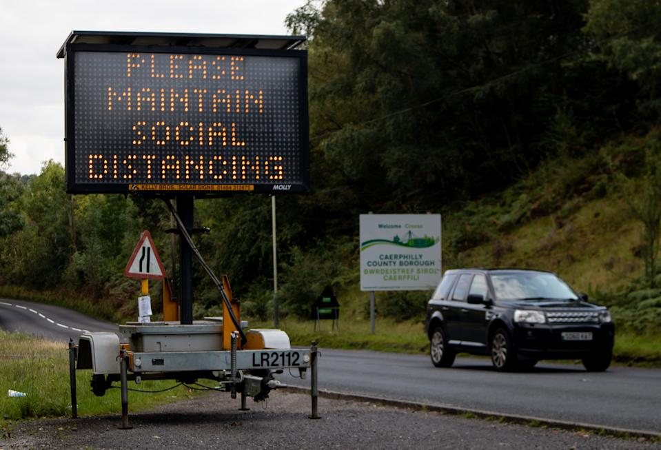 HOLLYBUSH, CAERPHILLY, WALES - SEPTEMBER 10:  A general view of a solar powered social distancing reminder sign which has been placed on the entry to Caerphilly Borough, where people are not allowed to enter or leave the Borough unless it is an essential journey, on September 10, 2020 in Hollybush, Wales, United Kingdom. The county borough of Caerphilly in South Wales is to be placed under a local lockdown from 18:00 BST on Tuesday, following a rapid rise in cases of coronavirus, in the first local lockdown in Wales. People will not be able to leave the borough without good reason and face masks will be required by everyone aged over 11 in shops. Seeing others within extended households indoors will also be banned. The Welsh government have said that with 55.4 cases per 100,000 population, Caerphilly county has the highest rate in Wales and one of the highest in the UK. (Photo by Huw Fairclough/Getty Images)