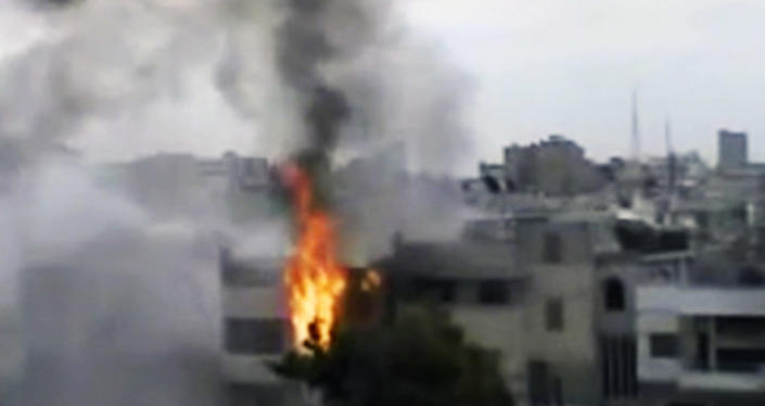 In this image made from amateur video released by the Shaam News Network and accessed Sunday, April 15, 2012, a building is on fire following purported shelling in Homs, Syria. Syrian troops are reported to have shelled residential neighborhoods dominated by rebels in the central city of Homs Sunday, activists said, killing at least three people hours before the first batch of United Nations observers were to arrive in Damascus to shore up a shaky truce. (AP Photo/Shaam News Network via AP video) TV OUT, THE ASSOCIATED PRESS CANNOT INDEPENDENTLY VERIFY THE CONTENT, DATE, LOCATION OR AUTHENTICITY OF THIS MATERIAL