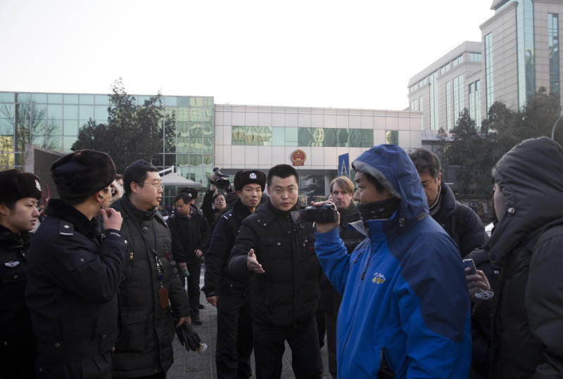 Chinese policemen urge foreign journalists to leave the Beijing's No. 1 Intermediate People's Court, where Xu Zhiyong is expected to stand trial, in Beijing Wednesday, Jan. 22, 2014. The trial of the prominent activist who has led a grassroots campaign demanding a fairer society and official accountability to better fight corruption started in Beijing, while police blocked journalists and supporters from getting near. Xu stood trial Wednesday, accused of disrupting public order. (AP Photo/Andy Wong)