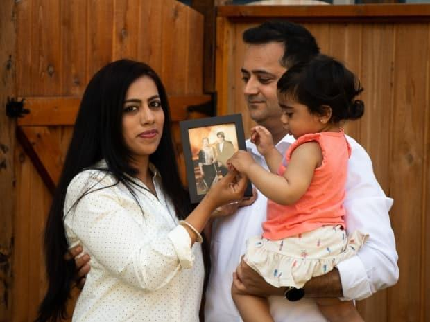 Nupur and Ajay Soin with their daughter Atishi hold up a picture of Nupur's son Shaurrya and his grandmother, at their home in Maple Ridge, B.C. The family has been waiting two and a half years for Shaurrya and Nupur's permanent residency visas.  (Maryse Zeidler/CBC - image credit)