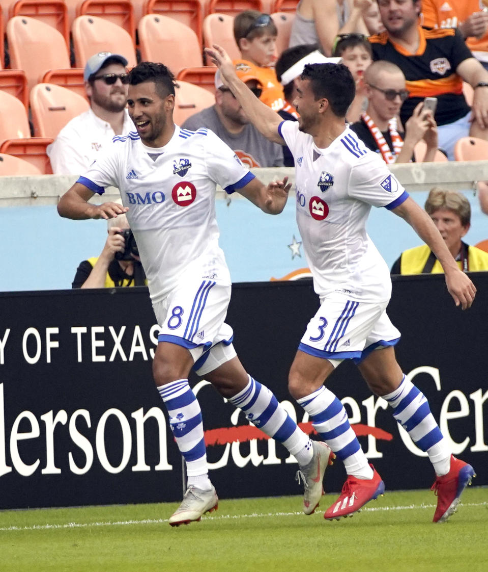 Montreal Impact's Saphir Taider (8) celebrates with Daniel Lovitz (3) after scoring a goal against the Houston Dynamo during the first half of an MLS soccer match Saturday, March 9, 2019, in Houston. (AP Photo/David J. Phillip)