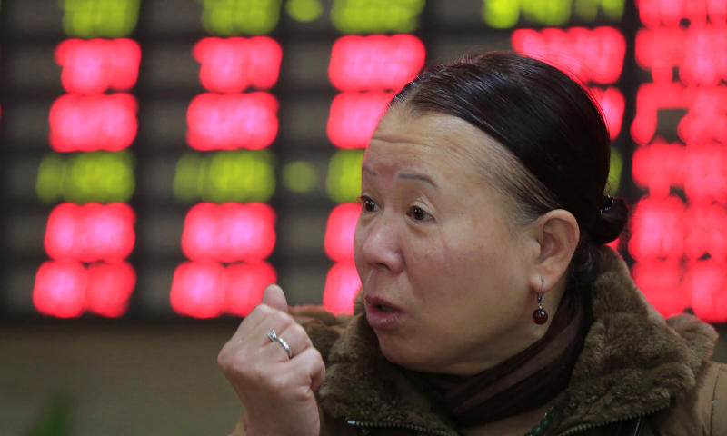 An investor gestures in front of the stock price monitor at a private securities company in Shanghai, China, Friday, Dec. 13, 2013. Asian stock markets mostly posted tentative gains Friday as investors prepared for the U.S. Federal Reserve's decision next week on whether to reduce its monetary stimulus. (AP Photo)