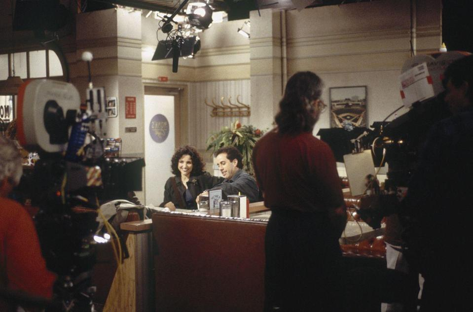 <p>This photo of the crew filming Elaine and Jerry sitting in the diner gives fans a look at the layout of the set. </p>