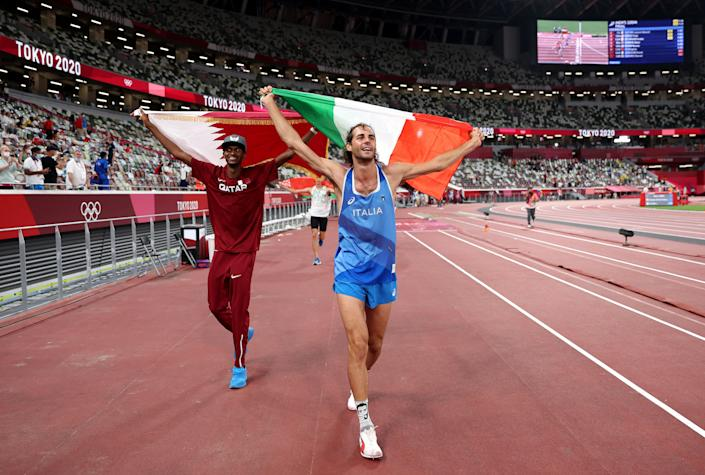 Gold medallists Mutaz Essa Barshim (left) of Qatar and Gianmarco Tamberi of Italy celebrate on the track following the men's high jump final at the 2020 Tokyo Olympics.