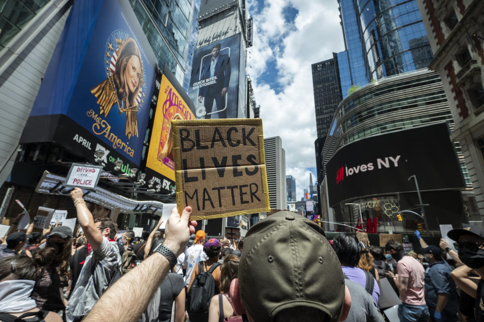 """MANHATTAN, NY - JUNE 07:  A Caucasian protester in Times Square holds up a handmade sign that reads, """"Black Lives Matter"""" with crowds of people around.  This was part of the Black Lives Matter New York (BLMNY) protest that offered a Blueprint for change and called on New York state legislators and members of Congress to end the slaughter of Black persons by the very institutions charged with protecting them.  The Blueprint is a policy platform to reform failed statutes and regulations and to  begin reforming to a more civil and just society. This includes the I Can't Breathe Act, the Blue Wall Act, repealing of 50-A statute and includes housing and education reforms. Protesters keep taking to the streets across America and around the world after the killing of George Floyd at the hands of a white police officer Derek Chauvin that was kneeling on his neck during his arrest as he pleaded that he couldn't breathe. The protest are attempting to give a voice to the need for human rights for African American's and to stop police brutality against people of color.  Many people were wearing masks and observing social distancing due to the coronavirus pandemic.  Photographed in the Manhattan Borough of New York on June 07, 2020, USA.  (Photo by Ira L. Black/Corbis via Getty Images)""""n""""n""""n"""