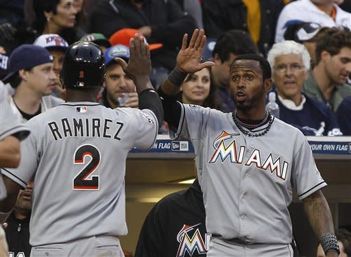 Miami Marlins' Hanley Ramirez is greeted at the dugout after scoring in the eighth inning against the San Diego Padres during a baseball game Saturday, May 5, 2012 in San Diego. (AP Photo/Lenny Ignelzi)
