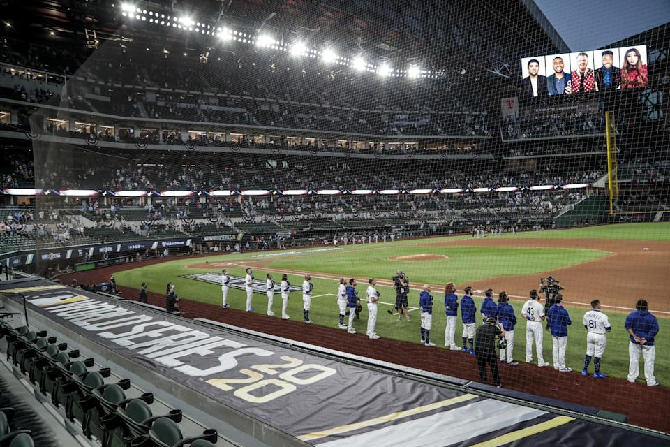 The Dodgers and the Tampa Bay Rays stand during the national anthem.