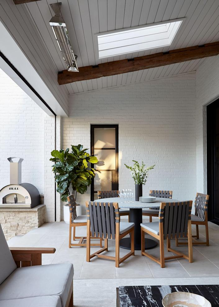 """This outdoor deck gets year-round warmth thanks to an electric heater installed on the ceiling and a wood-burning fireplace (not pictured). The stone-topped round table and the teak chairs with woven backs are from <a href=""""https://www.rodaonline.com/"""" rel=""""nofollow noopener"""" target=""""_blank"""" data-ylk=""""slk:Roda"""" class=""""link rapid-noclick-resp"""">Roda</a> via 1stDibs."""