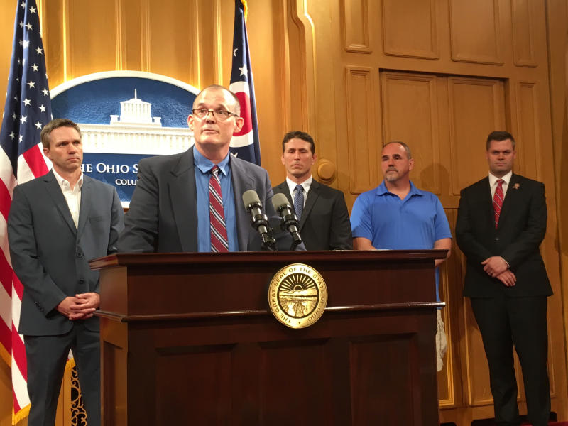 FILE - In a Tuesday, June 4, 2019 file photo, Roger Beedon discusses how sexual misconduct by now-deceased Ohio State team doctor Richard Strauss has affected his life, during a news conference with fellow Strauss accusers, from left, Brian Garrett, Dan Ritchie and Mike Flusche, and state Rep. Brett Hillyer, at the Statehouse in Columbus, Ohio. Men who say they were sexually abused by longtime Ohio State team doctor Richard Strauss are recounting how it changed their lives to make their case that the university owes them financial compensation. (AP Photo/Kantele Franko, File)
