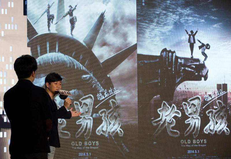 """Chinese film director and actor Xiao Yang, right, and actor Wang Taili, left, speak on stage as they promote their new movie """"Old Boys: The Way of the Dragon"""" in Beijing Thursday, Jan. 9, 2014. An online microfilm that was watched by millions and helped to establish a genre in China is to be made into a feature-length movie and shown in the country's cinemas. The planned debut of """"Old Boys"""" in China's cinemas in May after ratcheting up almost 70 million views on a video website demonstrates how online films are influencing the traditional film industry. (AP Photo/Andy Wong)"""
