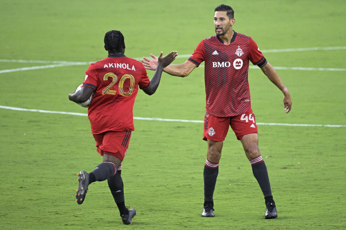 Toronto FC forward Ayo Akinola (20) is congratulated by defender Omar Gonzalez (44) after Akinola scored a goal during the first half of the team's MLS soccer match against Orlando City, Saturday, June 19, 2021, in Orlando, Fla. (AP Photo/Phelan M. Ebenhack)