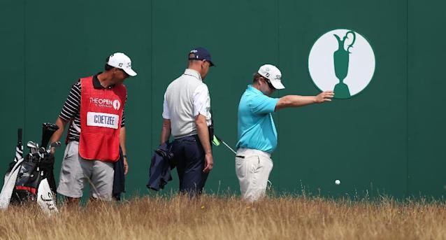 George Coetzee of South Africa is watched by his caddie and a member of the rules committee as he takes a drop shot on the 18th during the second day of the British Open Golf championship at the Royal Liverpool golf club, Hoylake, England, Friday July 18, 2014. (AP Photo/Jon Super)