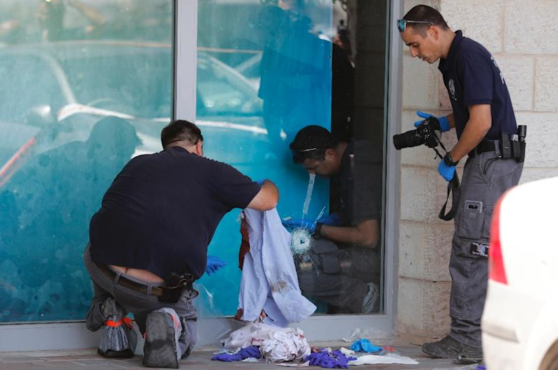 Israeli forensic policemen inspect the site where an Israeli man was fatally stabbed by a Palestinian near a mall at the Gush Etzion junction near Bethlehem in the occupied West Bank on September 16, 2018