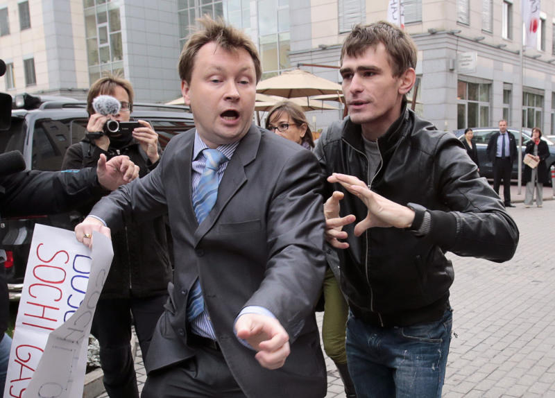 An unidentified man chases gay rights activist Nikolai Alexeyev (L), who is protesting against a ban on staging a gay pride parade during the Sochi 2014 Winter Olympic Games, in front of the Sochi 2014 organizing committee building in Moscow, September 25, 2013. REUTERS/Tatyana Makeyeva (RUSSIA - Tags: SOCIETY CIVIL UNREST SPORT OLYMPICS)