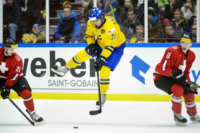Sweden's Anton Karlsson is in the air after a tackle from Switzerland's Fabrice Herzog (R) during their IIHF World Junior Hockey Championship ice hockey game in Malmo December 26, 2013. Also pictured at left is Marco Muller. REUTERS/Ludvig Thunman/TT News Agency (SWEDEN - Tags: SPORT ICE HOCKEY) ATTENTION EDITORS - THIS IMAGE WAS PROVIDED BY A THIRD PARTY. THIS PICTURE IS DISTRIBUTED EXACTLY AS RECEIVED BY REUTERS, AS A SERVICE TO CLIENTS. SWEDEN OUT. NO COMMERCIAL OR EDITORIAL SALES IN SWEDEN. NO COMMERCIAL SALES