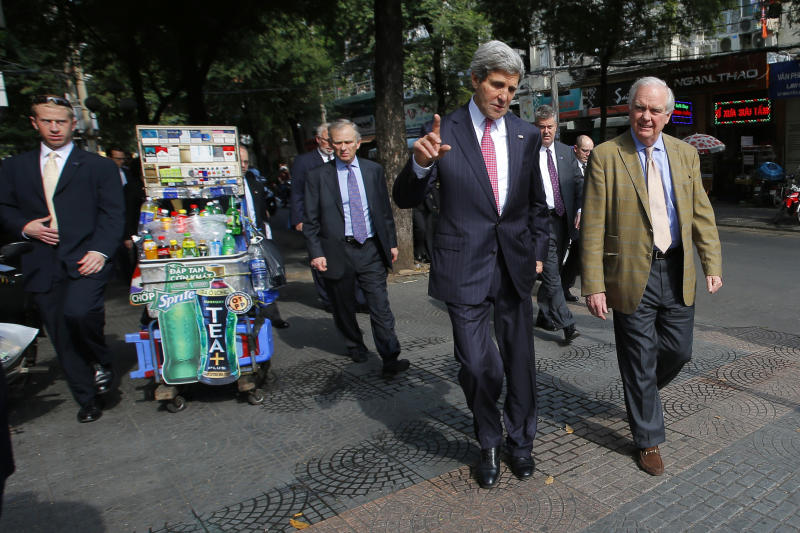 U.S. Secretary of State John Kerry, second from right, and his friend and fellow Vietnam War veteran Tommy Vallely, right, walk along a street in Ho Chi Minh City, Vietnam, to attend a service at the Notre Dame Cathedral Saturday, Dec. 14, 2013. Forty-four years after first setting foot in Vietnam as a young naval officer, Kerry returned once more, this time as America's top diplomat. (AP Photo/Brian Snyder, Pool)
