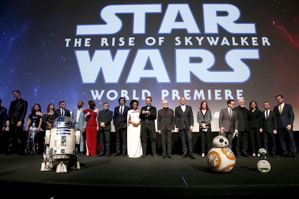 "HOLLYWOOD, CALIFORNIA - DECEMBER 16: (L-R) Anthony Daniels, Billy Dee Williams, Joonas Suotamo, Kelly Marie Tran, Keri Russell, Oscar Isaac, John Boyega, Daisy Ridley, Mark Hamill, Adam Driver, Naomi Ackie, Richard E. Grant, Ian McDiarmid, The Walt Disney Company Chairman and CEO Bob Iger, Producer and President of Lucasfilm Kathleen Kennedy, Director, Writer and Producer J.J. Abrams, composer John Williams, producer Michelle Rejwan, Writer Chris Terrio and executive producer Callum Greene speak onstage during the World Premiere of ""Star Wars: The Rise of Skywalker"", the highly anticipated conclusion of the Skywalker saga on December 16, 2019 in Hollywood, California. (Photo by Jesse Grant/Getty Images for Disney)"
