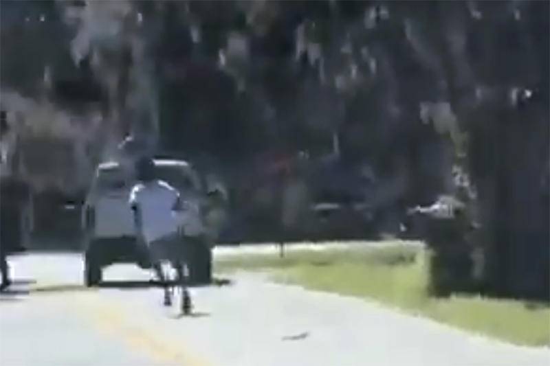 ADDS THAT THE AP HAS NOT BEEN ABLE TO VERIFY THE SOURCE OF THE VIDEO - This image from video posted on Twitter Tuesday, May 5, 2020, purports to show Ahmaud Arbery running on a street in a neighborhood outside Brunswick, Ga., on Feb. 23, 2020, as a pickup truck is stopped in front of him. Two men in the truck, Travis McMichael and his father, Gregory McMichael, confronted Arbery and less than a minute later he was fatally shot. The AP has not been able to verify the source of the video. (Twitter via AP)