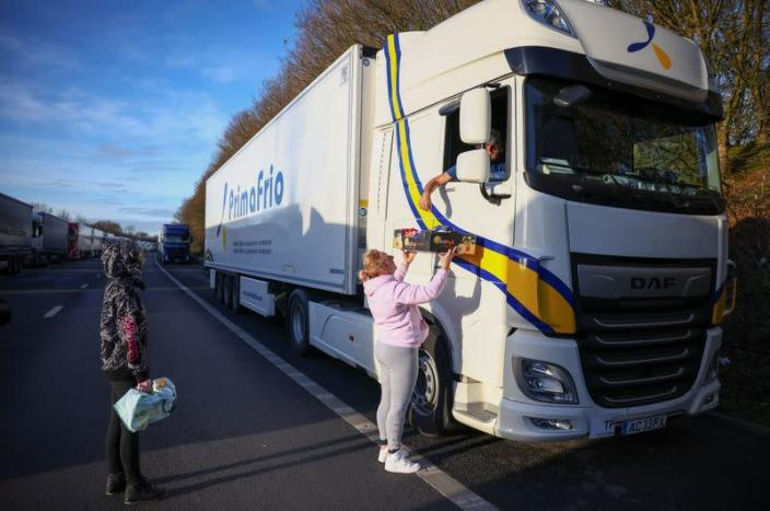 A woman hands out donated food to a lorry driver on the outskirts of Ashford