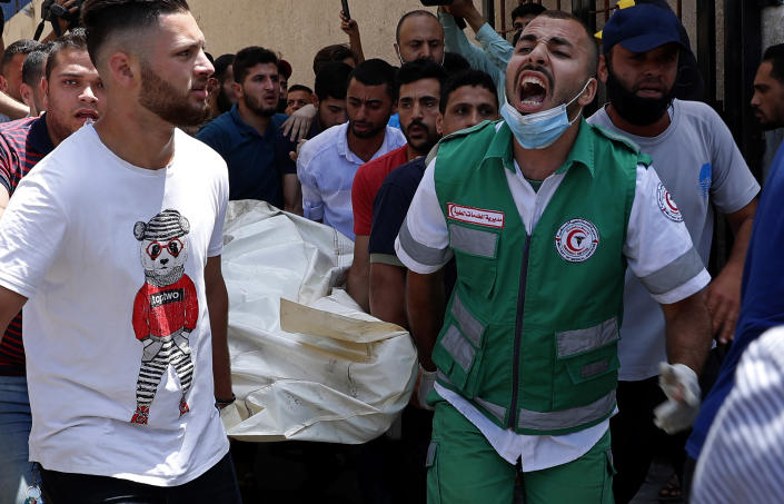 Medics and youths chant while carrying the covered body of a man, who was killed in Israeli airstrikes that hit his apartment building, in Gaza City, Tuesday, May 11, 2021. Since Monday, Gaza militants have fired hundreds of rockets toward Israel. Israel has fired back, hitting targets inside Gaza that included a high-rise building in the middle of Gaza City. (AP Photo/Adel Hana)
