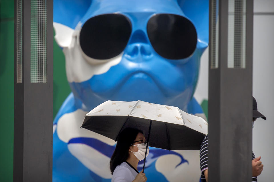 A woman wearing a face mask to protect against the new coronavirus walks past a statue at an outdoor shopping mall in Beijing, Saturday, July 4, 2020. China reported a single new case of coronavirus in Beijing on Saturday, plus a few more cases elsewhere believed to have come from abroad. (AP Photo/Mark Schiefelbein)