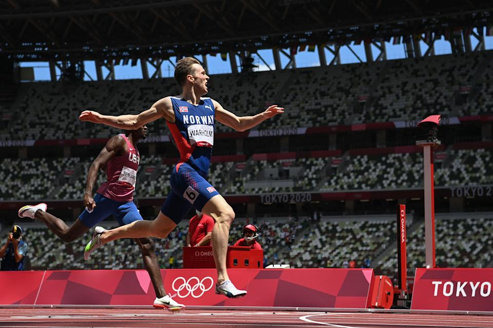 <p>Norway's Karsten Warholm crosses the finish line to win break the world record in the men's 400m hurdles final during the Tokyo 2020 Olympic Games at the Olympic Stadium in Tokyo on August 3, 2021. (Photo by Jewel SAMAD / AFP)</p>