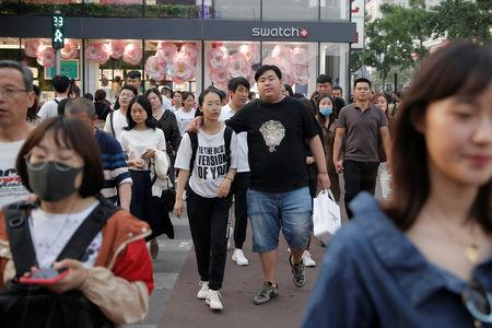 People walk in Wangfujing shopping street in Beijing, China May 15, 2019.  REUTERS/Thomas Peter