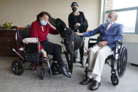 Sal Markowitz, 96, right, and Sandra Greer, 82, left, visits with Marley, a Great Dane, while therapeutic activities director Catherine Farrell looks on at The Hebrew Home at Riverdale in New York, Wednesday, Dec. 9, 2020. New dog recruits are helping to expand the nursing home's pet therapy program, giving residents and staff physical comfort while human visitors are still restricted because of the pandemic. (AP Photo/Seth Wenig)
