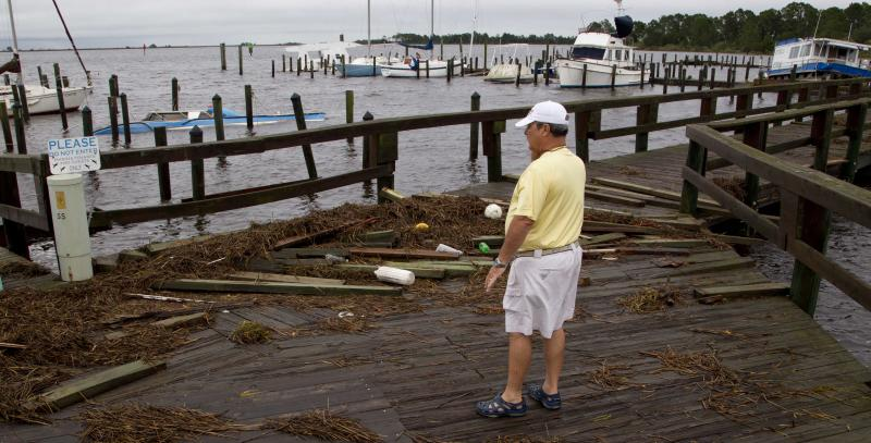 Mark Mitchell surveys the damage to boats at the Rock Landing Marina in Panacea, Fla., Tuesday, June 26, 2012. High winds and heavy rains spawned by the approaching Tropical Storm Debby caused the damage. (AP Photo/Dave Martin)