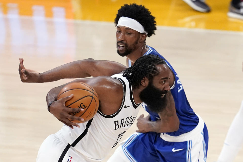 Brooklyn Nets guard James Harden, left, dribbles around Los Angeles Lakers guard Kentavious Caldwell-Pope during the first half of an NBA basketball game Thursday, Feb. 18, 2021, in Los Angeles. (AP Photo/Marcio Jose Sanchez)