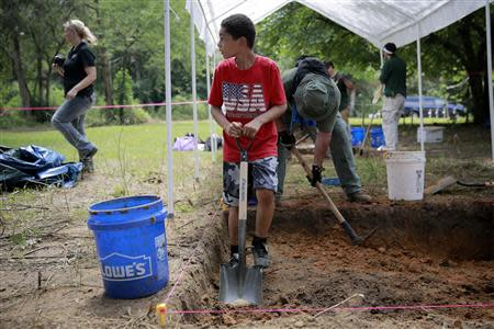 Jason Due, 9, helps University of South Florida researchers exhume a grave at the Boot Hill cemetery at the Boot Hill cemetery at the now closed Arthur G. Dozier School for Boys in Marianna, Florida, August 31, 2013. REUTERS/Edmund D Fountain/Pool