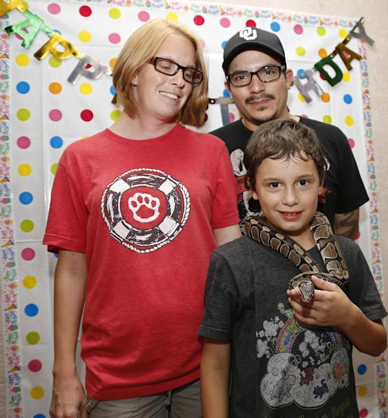 In this Monday, Aug. 5, 2013 photo, Xavier Delgado, front, poses for a photo with his pet snake, his mother, Athena Delgado, left, and father, Simon Delgado, right, in front of a birthday banner at his tenth birthday party in Moore, Okla. Athena says that her son isn't especially afraid of storms after the tornado, but has become more obsessed with tornadoes and learning more about them. Xavier lost six of his classmates in the tornado. (AP Photo/Sue Ogrocki)