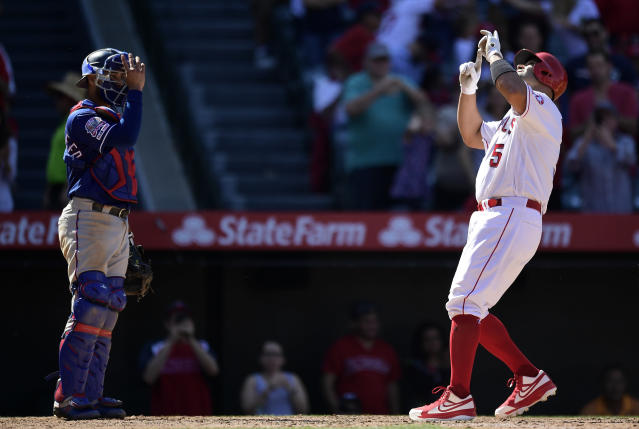 Los Angeles Angels' Albert Pujols, right, gestures after hitting a solo home run as Texas Rangers catcher Isiah Kiner-Falefa stands at the plate during the seventh inning of a baseball game Saturday, April 6, 2019, in Anaheim, Calif. (AP Photo/Mark J. Terrill)