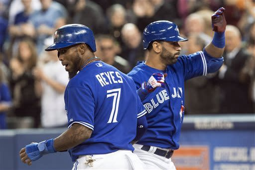 Toronto Blue Jays' Jose Bautista, right, celebrates with Jose Reyes after hitting a two-run home run off Cleveland Indians starting pitcher Brett Myers during the first inning of a baseball game in Toronto on Thursday, April 4, 2013. (AP Photo/The Canadian Press, Chris Young)