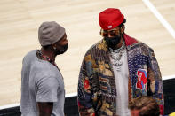Atlanta Falcons wide receiver, Julio Jones, talks with rapper 2 Chainz during the second half of an NBA basketball game Wednesday, May 12, 2021, in Atlanta. Atlanta Hawks defeated the Washington Wizards 120-116. (AP Photo/Butch Dill)