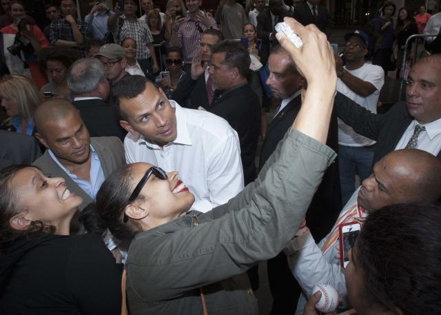 New York Yankees baseball player Alex Rodriguez (C, in white) poses for a photo with a supporter after leaving Major League Baseball's headquarters in New York, October 4, 2013. Yankees' Rodriguez has sued Major League Baseball (MLB) and Commissioner Bud Selig and accused them of trying to destroy his reputation and his career. MLB responded to the lawsuit by issuing their own statement, denying the allegations made by Rodriguez and accusing him of trying to circumvent the grievance process of the league and its players. REUTERS/Carlo Allegri (UNITED STATES - Tags: CRIME LAW DRUGS SOCIETY SPORT BASEBALL)